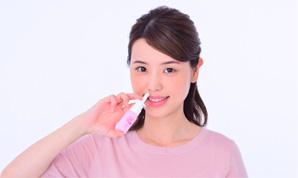 スプレーを押して鼻を洗浄する